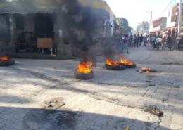 Hořící pneumatiky v ulicích města Hinche na Haiti; Foto: Hlas Ameriky / Wikimedia Commons