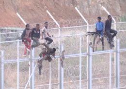 Afričtí imigranti se snaží přelézt plot do španělské enklávy Ceuta; Reprofoto: YouTube.com